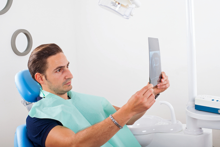 Male patient examining his dental x-ray Stock Photo