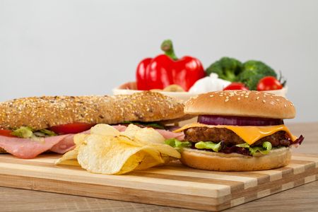 Fresh ciabatta sandwich with pork ham and veggies, delicious cheeseburger and potato chips on a wooden cutting board