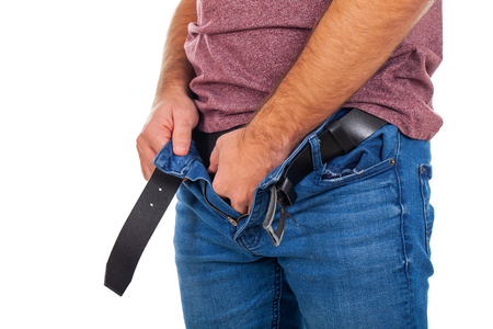 Close up picture of young man with unzipped jeans and  holding his genitals Stock Photo