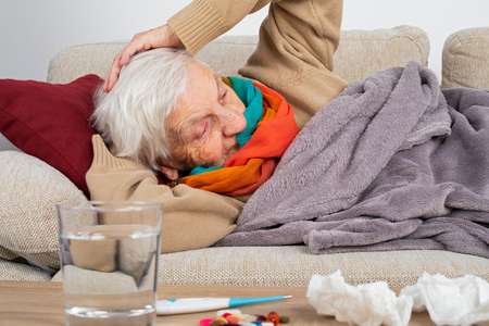 Senior woman feeling sick is lying on the couch wrapped in a blanket - Influenza, sore throat, headache - Medication, tissues and water in front of her