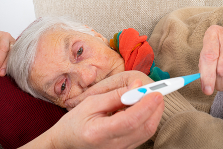 Close up picture of sick elderly woman resting on the sofa, caregivers hand holding her hands - seasonal influenza