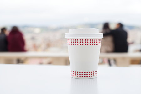 Capuccino in a white paper cup on a table - coffee terrace with panoramic view Stockfoto