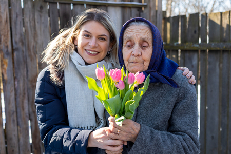 Young woman giving a bouquet of pink tulips to her elderly grandmother  on Womens day, 8th of March. Love, care, gift, togetherness