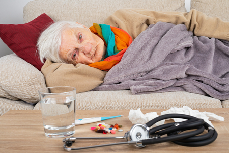 Senior woman lying on the couch wrapped in a blanket, having a bad flu - water, medication and stethoscope on the table in front of her