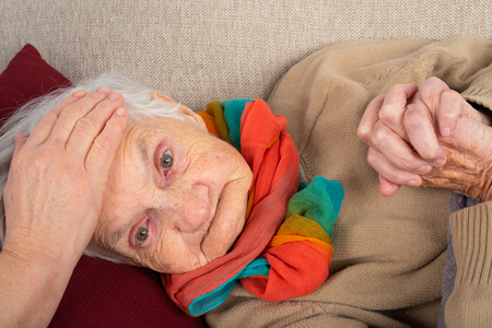 Close up picture of sick elderly woman with fever resting on the sofa, caregivers hands holding her