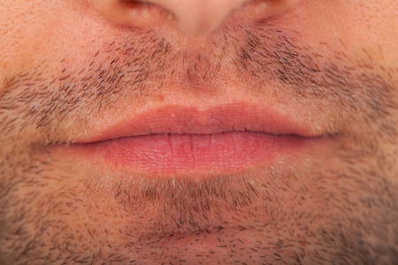 Close up picture of young mans bristle and mouth. Facial hair macro