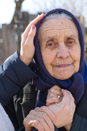 Portrait of an elderly caucasian woman and caregiver's hands outdoor - support, love, care Archivio Fotografico