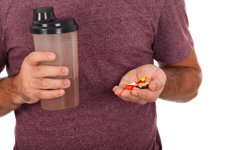 Close up picture of a young man holding a protein shake and some pills - isolated background