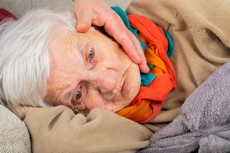 Close up portrait of a sad elderly wrinkled woman lying on the couch, wearing colorful scarf - caregiver's hand touching her face
