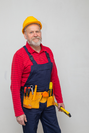 Portrait of an elderly repairman with uniform, yellow hard hat and tool belt working at a new residential home