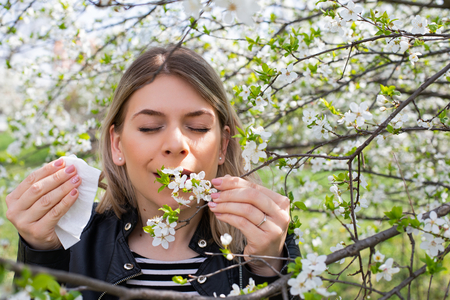 Young woman with allergy symptoms, sneezing, blowing her nose, springtime Banco de Imagens