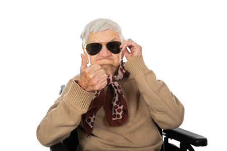 Blind elderly lady sitting in a wheelchair on isolated background