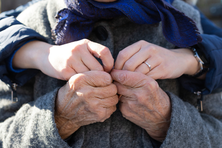 Close up picture of young female hands  holding old woman's wrinkled hands - love, affection, embrace, help for the elderly 스톡 콘텐츠