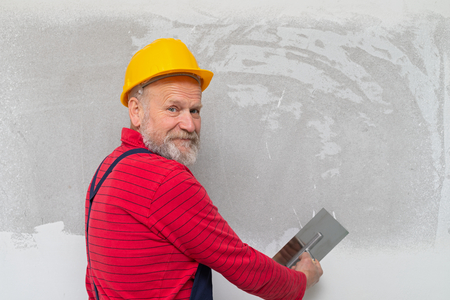 Picture of a senior worker holding a spatula filling in the walls in a new apartment Banco de Imagens