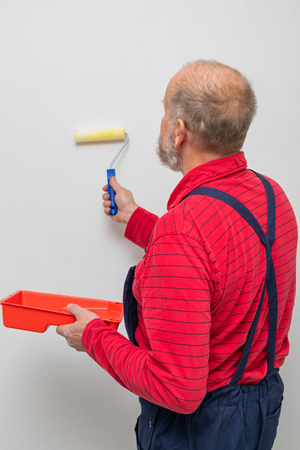 Picture of a senior worker painting the walls in a brand new apartment - finishing concept