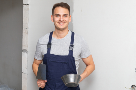 Picture of a  worker holding a spatula filling in the walls in a new apartment Stock Photo