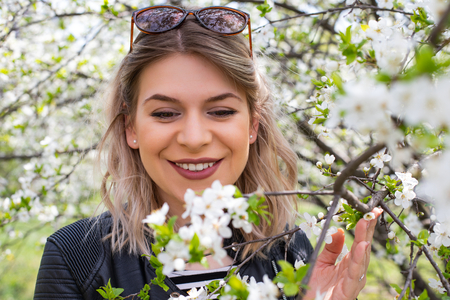 Portrait of an attractive young woman outdoor in blooming garden, springtime Stock Photo