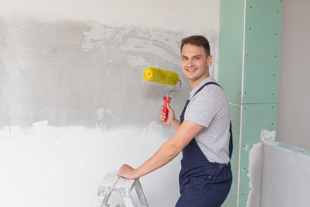 Picture of a young worker painting the walls in a brand new apartment - finishing concept Banque d'images - 122268419