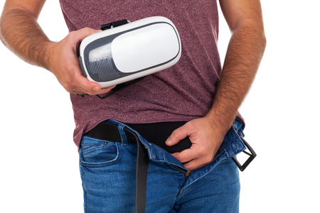 Picture of a man holding his penis and a VR headset