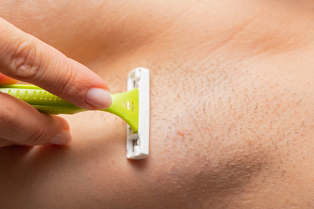 Close up picture of hairy armpit, woman shaving with razor