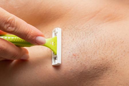 Nahaufnahme Bild von behaarter Achselhöhle, Frau, die sich mit Rasiermesser rasiert