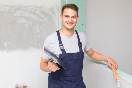 Picture of a young cheerful repairman working at the bathroom walls in new apartment - concrete walls Stock Photo
