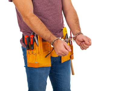 Illegal craftsman with yellow tool beltin handcuffs