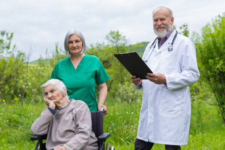 Aged woman with dementia sitting in a wheelchair, male doctor and female nurse taking care of her outdoor - assisted living
