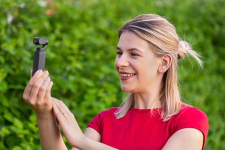 Young beautiful woman holding DJI Osmo Camera, ideal device for travel videos and photos