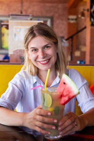 Donna che mantiene una limonata rinfrescante fredda su una terrazza sulla spiaggia in una calda giornata estiva