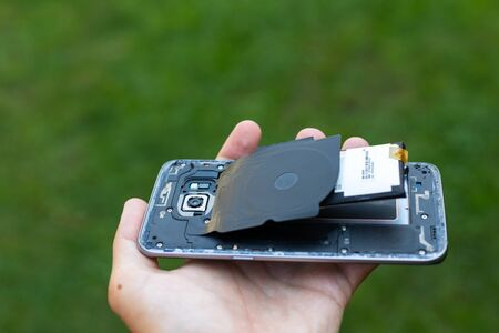 Close up of a damaged smartphone with expanded lithium ion battery Archivio Fotografico