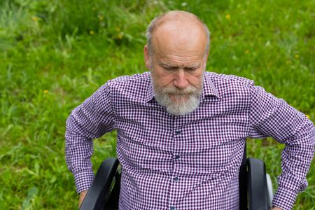 Picture of an elderly man  sitting in a wheelchair spending time outdoor in the park