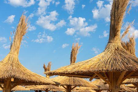 Reed beach umbrella at the seashore against blue cloudy sky Stock fotó