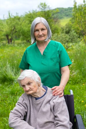 Old woman with severe dementia sitting in a wheelchair is spending time outdoor with friendly caregiver
