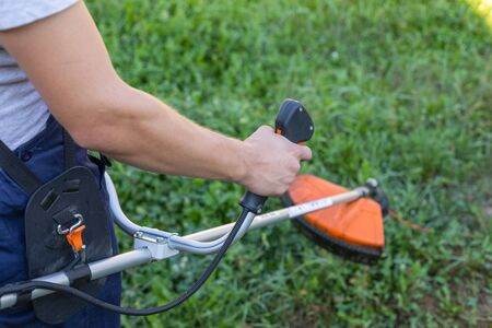 Young gardener cutting the grass with a petrol lawn mower