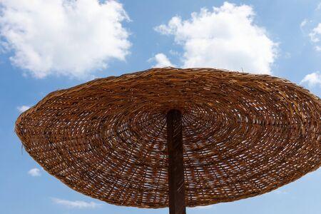 Reed beach umbrella at the seashore against blue cloudy sky