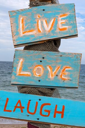 Quotes on wooden colorful signs at Vama Veche beach, Romania