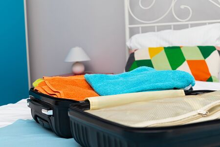 Traveler suitcase full of clothes at cozy modern apartment