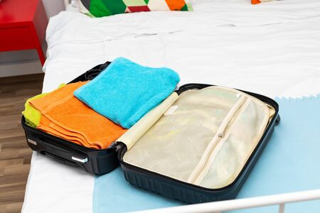 Traveler suitcase full of clothes at cozy modern apartment Фото со стока - 130818476