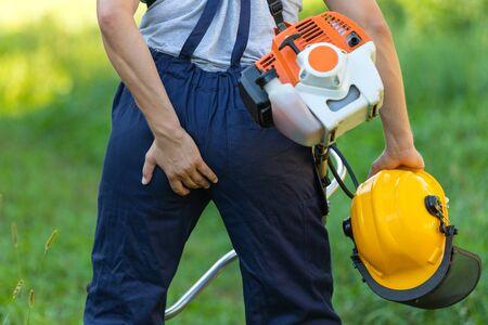 Young gardener having diarrhea while cutting the grass