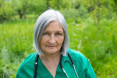 Portrait of a mature medical nurse looking to the camera outdoor