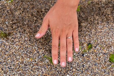 Woman showing her engagement ring within a heart sign on the wet sand