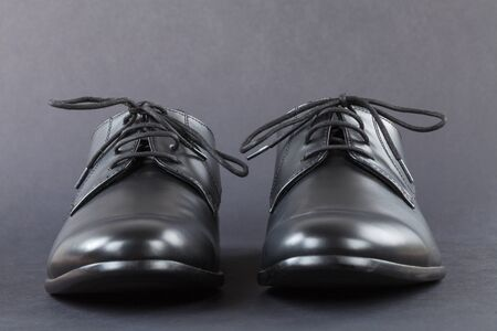 Close up picture of mens footwear. Black leather elegant shoes on grey background