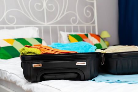 Traveler suitcase full of clothes at cozy modern apartment Фото со стока - 130818564