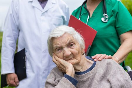 Portrait of elderly woman in wheelchair with dementia disease, doctor and nurse in the background, outdoor