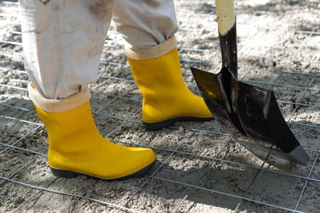 Construction worker in yellow rubber boots at the construction site, compacting the concrete