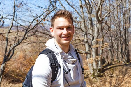 Portrait of a young man smiling to the camera while on a hiking adventure, sunny day