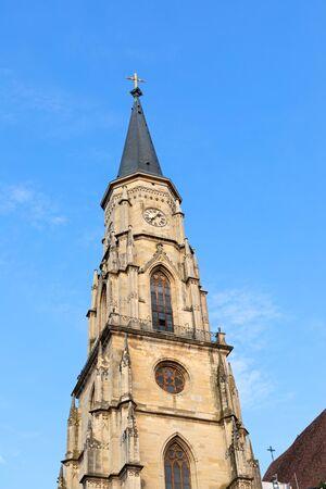 Tower of St Michael catholic church against blue sky in Cluj-Napoca city center, Transylvania