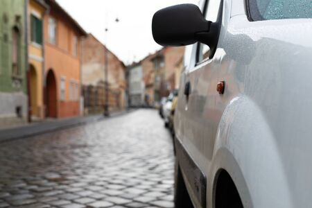 Scenic picture of a street in Sibiu medieval center, cars parked along the road Imagens