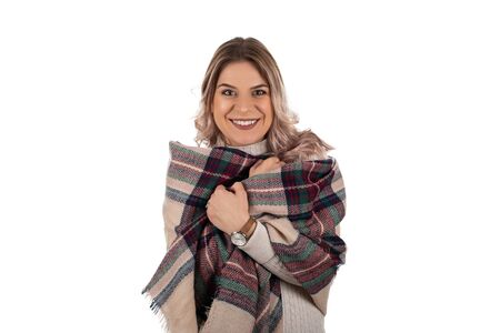 Beautiful young woman wrapped up in a trendy winter scarf is smiling to the camera on isolated